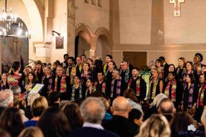 choristes lors d'un concert de la chorale gospel Sunday Voices habillés en noir avec des écharpes colorées